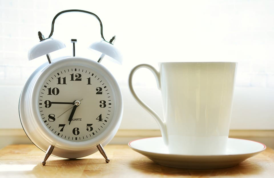 A white alarm clock next to a mug.