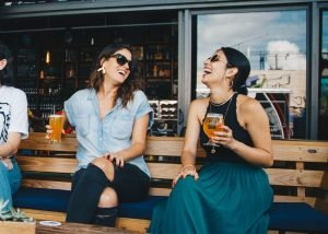 Two girls laughing and holding beer in glasses