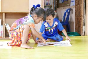 two children reading a book on the floor