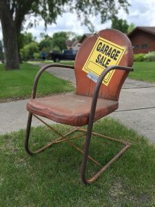 a red chair with a garage sale sign written on it