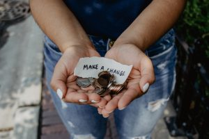 donate your stuff before moving- hands with change and a paper that says- make a change