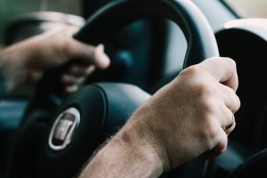 a person holding a steering wheel