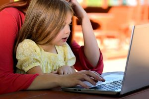 a child sitting in his mother`s lap looking at the laptop