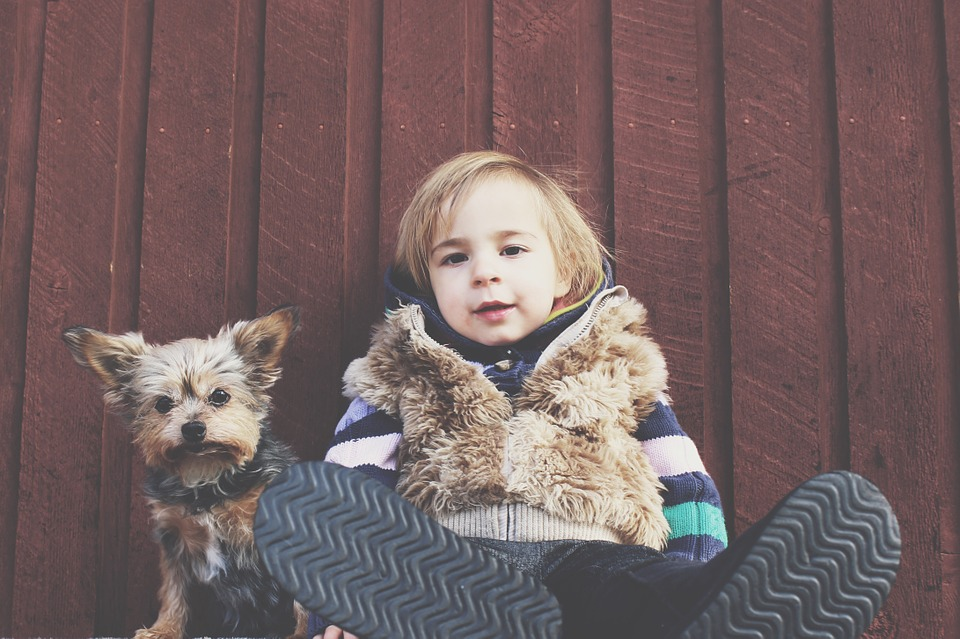 a boy and his dog sitting down in front of a wall