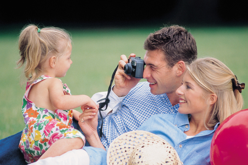 parents in the park, photographing their daughter