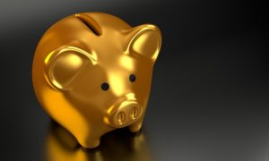 a gold piggy bank on a dark surface