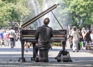 Places to visit after moving to Queens - A man playing the piano in a park