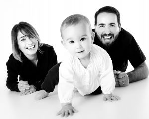 a mother, father and a toddler on a white surface, a black and white photo of a family