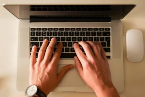 man`s hands with a wrist watch typing on laptop