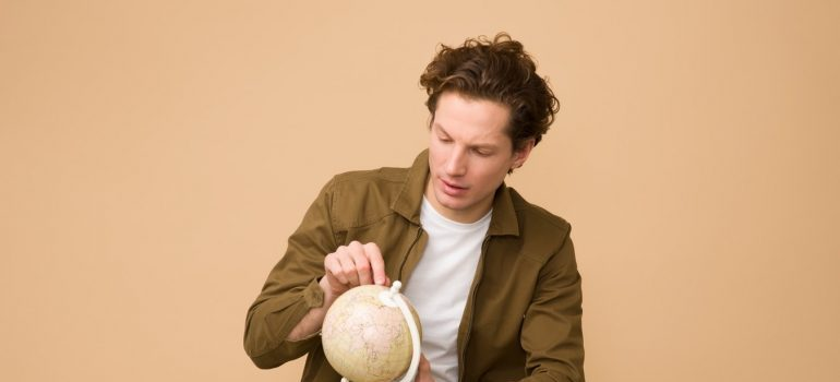 A man playing with a mini globe