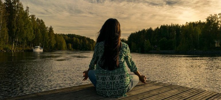 A woman doing yoga near a lake with a forest in the distance