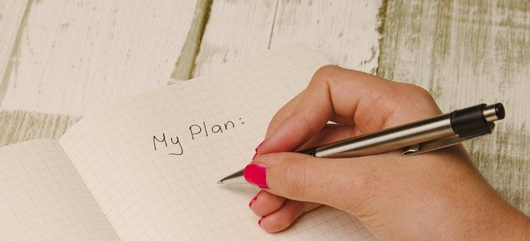 person writing down a plan on how to move to Long Island without a job
