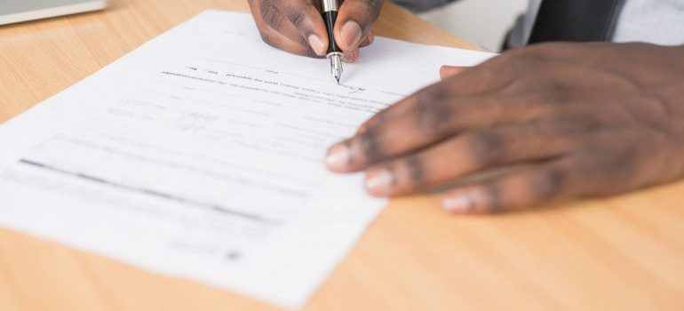 Man doing paperwork on a table.