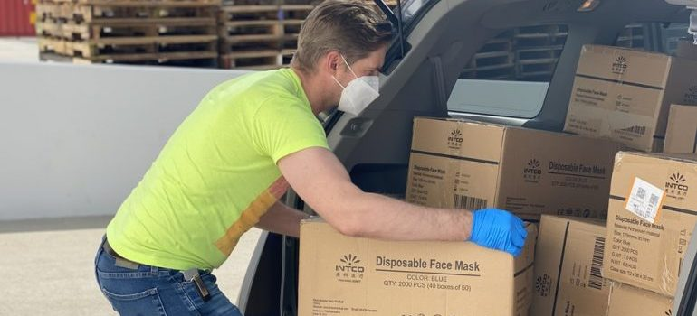 A man packing boxes in his car