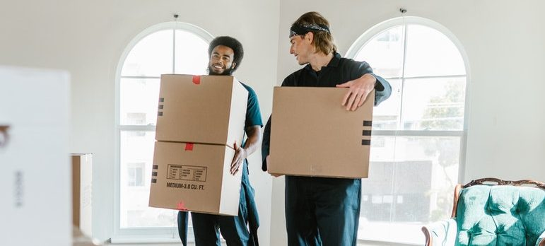 Two movers carrying carton boxes