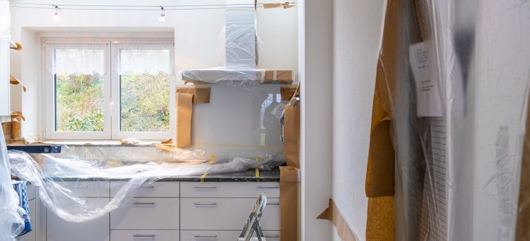 White kitchen elements in front of the window wrapped and protected awaiting renovation to start while you are deciding should you move out while renovating