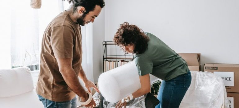 A couple using plastic wrap as packing mistakes to avoid.