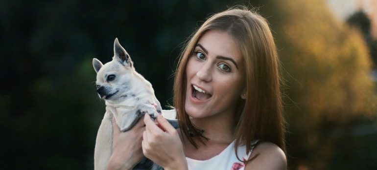 A woman holding a dog smiling.