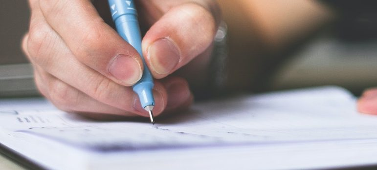A person writing on the paper