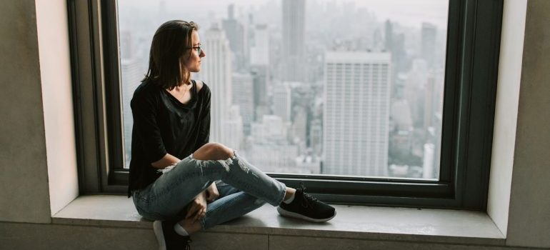 A woman looking at NYC sitting on the window