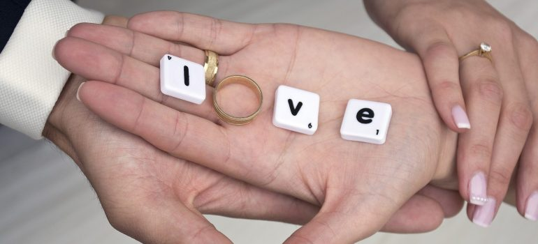 Man and woman holding hands and on hands a word LOVE with a ring standing for the letter O.